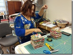 Adriana is packaging fat quarter bundles for Festival at Houston